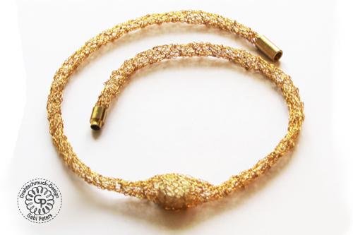 Dieses goldene Collier ist mit einem Golddraht gehäkelt worden.