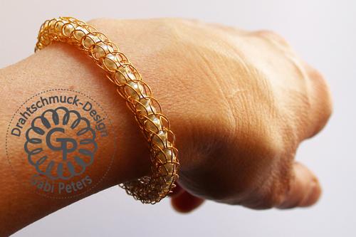 goldenes Strickarmband aus Draht mit weißen Perlen